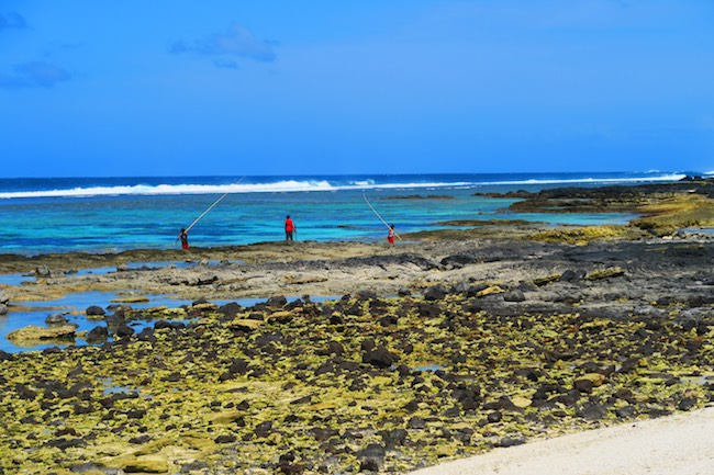 Children fishing in Salamumu Tropical Beach Samoa