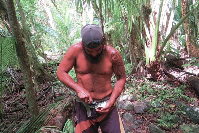 Halawa Valley Hike - Guide opening coconut - Molokai Hawaii