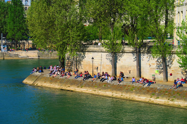 People sitting along the banks of the Seine paris