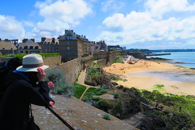 woman with hat on city wall saint malo