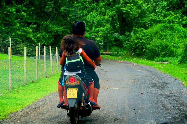 Child riding back of motorbike in Rarotonga Cook Islands
