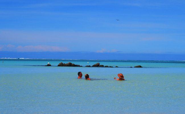 Motu beach Les Tipaniers Moorea French Polynesia people in lagoon