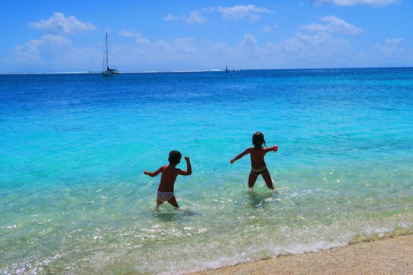 children tossing rocks Fare beach Huahine Island French Polynesia