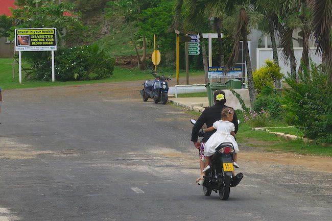Mom and daughter scooter sunday church aitutaki