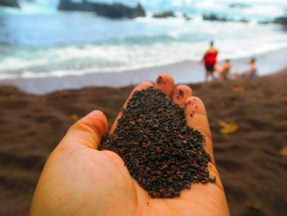 Holding soil in Kaihalulu Red Sand Beach - road to Hana - Maui Hawaii