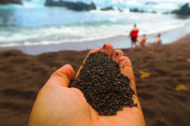 Holding soil in Kaihalulu Red Sand Beach - road to Hana - Maui Hawaii