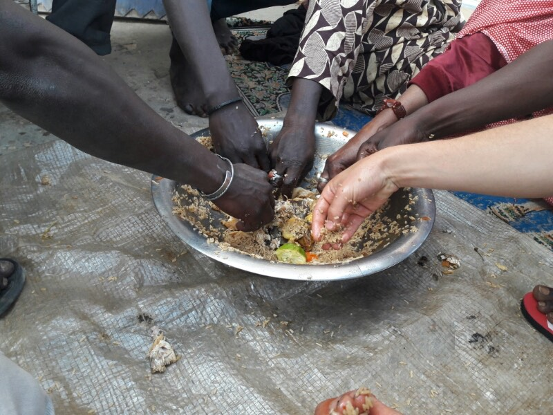 Sharing food on the street with locals in Senegal - Vagabjorn