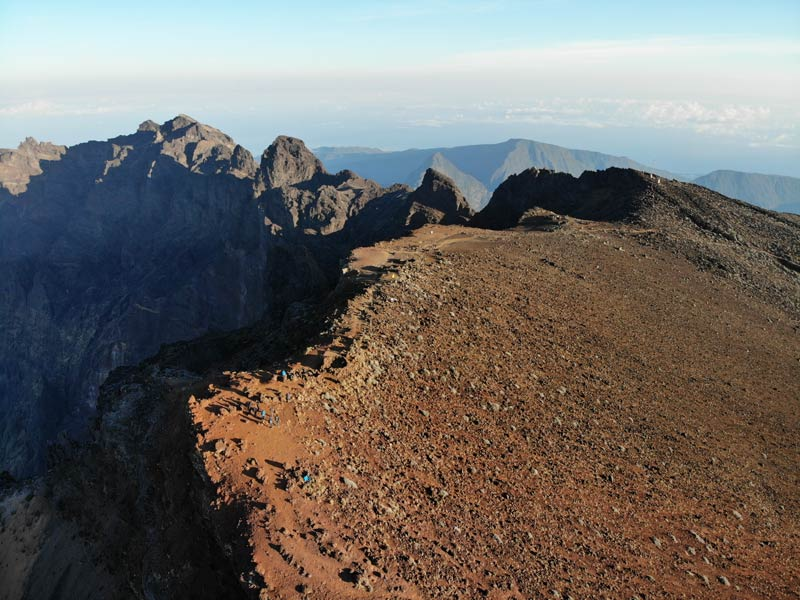 Summit of Piton des Neiges Hike - Reunion Island - Hikers at summit red earth